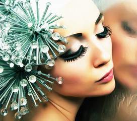Fashion hairstyle model reflects in mirror - bright makeup