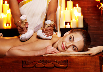 Woman having massage with pouch of rice.