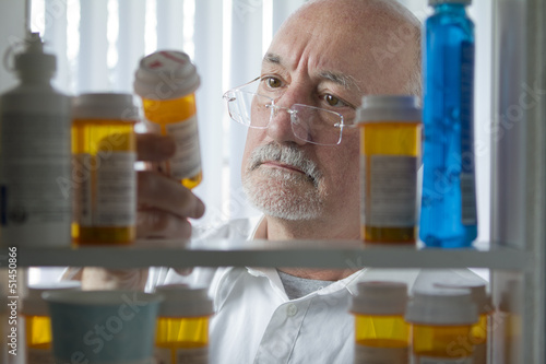 Man reaching for prescription form medicine cabinet