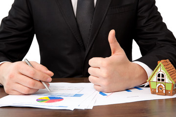 businessman sitting at the table with house and sign a contract