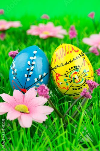 Leinwandbild Motiv Colorful easter eggs in a row on green grass