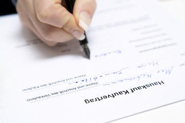 Hauskauf Kaufvertrag wird mit Füller ausgefüllt
