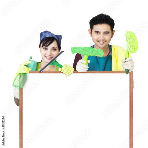 Cleaning service couple holding copyspace