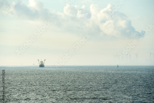 Industrial harbor with wind turbines and fishing boat