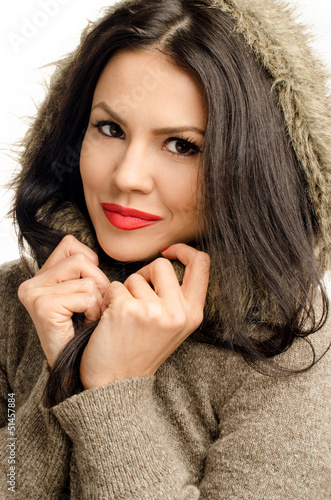 Young attractive woman wearing a sweater with faux fur hood.