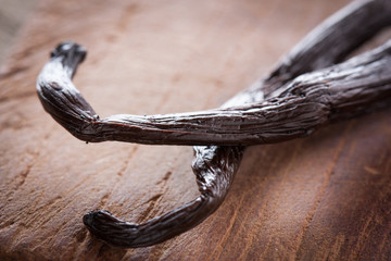 Black vanilla sticks on wooden table
