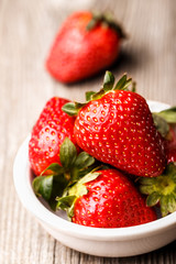 Strawberries in white plate on the old wooden surface.