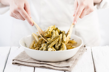 Cook mixing pesto with penne rigate pasta