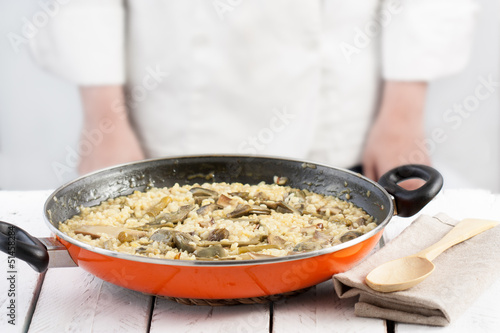 Cook standing behind a pan on vegetables rice