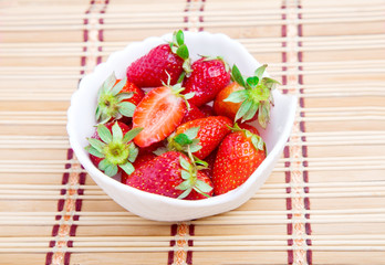 Bowl of strawberries on straw mat