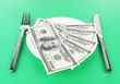 Money on plate on green background