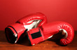 Boxing gloves on wooden table, on red background