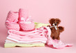 Pile of baby clothes on pink background
