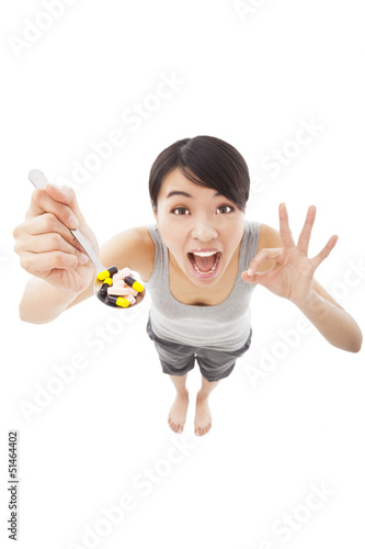 young woman holding pills with ok gesture