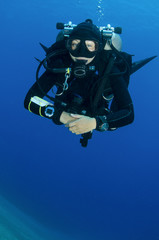 girl scuba dives in clear blue water with twin tanks