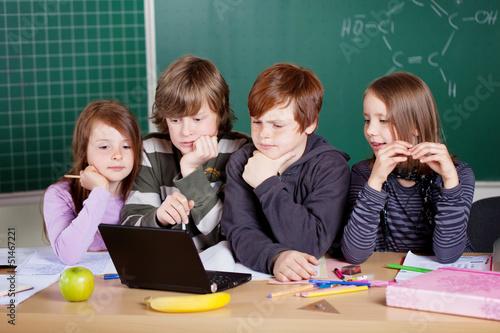 schüler schauen auf laptop