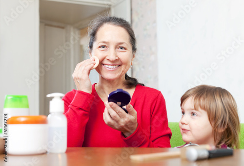 grandmother with granddaughter puts facepowder