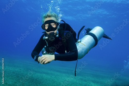young atractive girl scuba dives in clear blue water