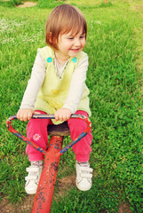 Happy little girl swinging on see-saw
