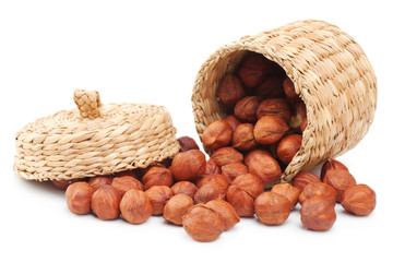 hazelnuts and basket on white