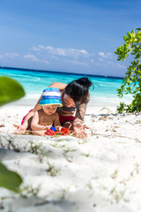 Tattooed mother with her baby on a beautiful beach