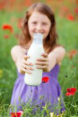 mädchen zeigt eine flasche milch