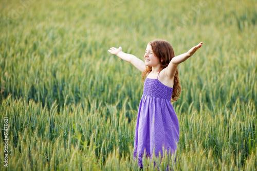 kleines mädchen steht im kornfeld