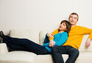 Dreaming young couple on sofa in home interior