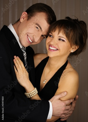 Happy young elegant couple in classic dress embracing