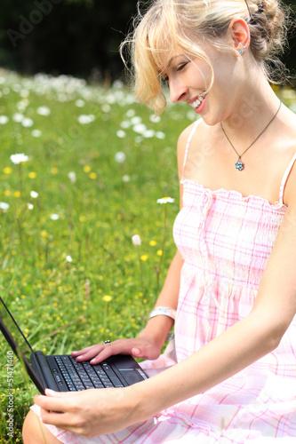 mit laptop auf der grünen wiese