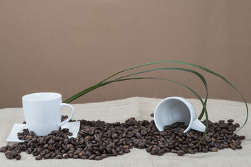 Dos tazas de café entre granos naturales.
