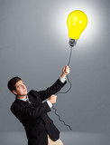 Handsome man holding light bulb balloon