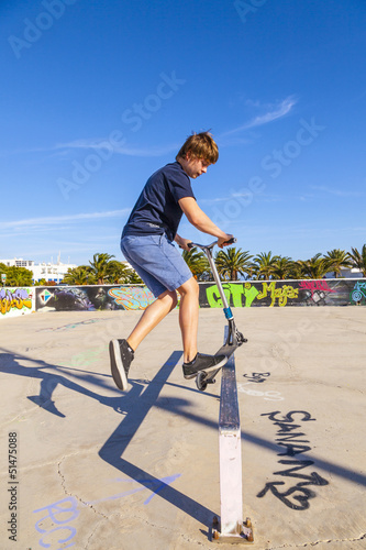 boy has fun with his scooter at the skate park