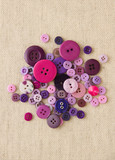 Pile of purple buttons on hessian