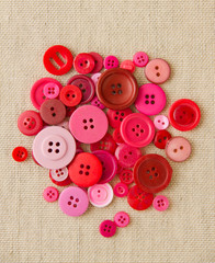 Pile of red and pink buttons on hessian
