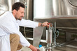 Beer brewer in his brewery at food tank