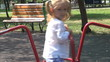 Child Playing at Playground, Spinning on Merry-Go-Round