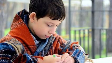 School age boy draws something outdoor