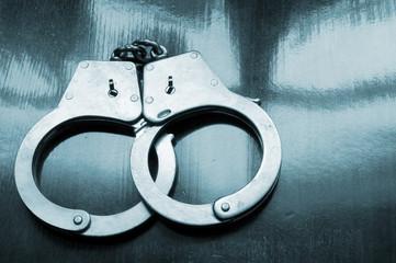 Steel metallic handcuffs on wooden table