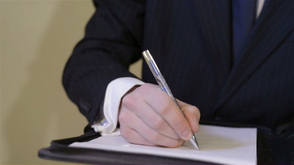 Businessman writing and signing a contract