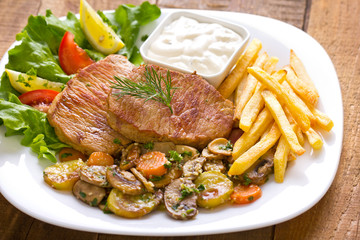 Pork chop with French fries and vegetables