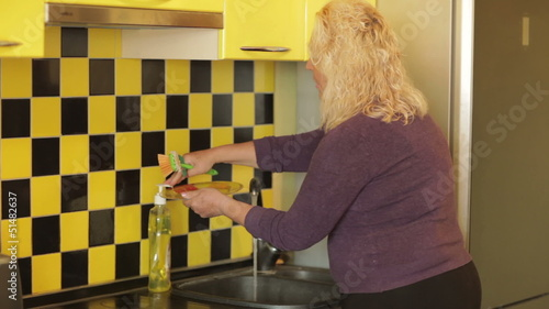 Middle-aged woman washing a plate in the kitchen.