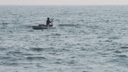 lone fisherman floating in sea on fishing - Kerala India
