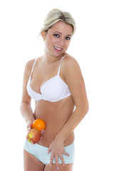 Blondine in Unterwäsche hält Früchte vor Bauch