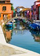 Channel in Burano island full of boats and colorful houses
