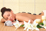Fototapety Beautiful relaxing woman with stones on her back in a Spa