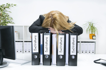 Frau im Büro mit dem Kopf auf Aktenordnern der Buchhaltung