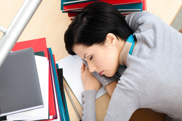 Female student sleeping at the desk with piles of books