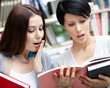 Two beautiful female students read books at the library