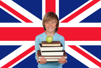 Happy Boy Holding Stack Of Books With Apple